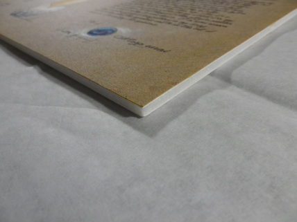 The edge of the finished piece, showing the foamcore board that supports it.